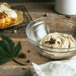 Cannabis-infused Chai Cream Cheese Frosting in a glass bowl with a marijuana leaf, and cinnamon buns